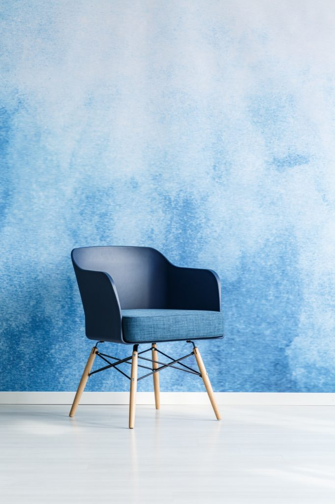 Single modern navy blue chair standing against empty blue and wh